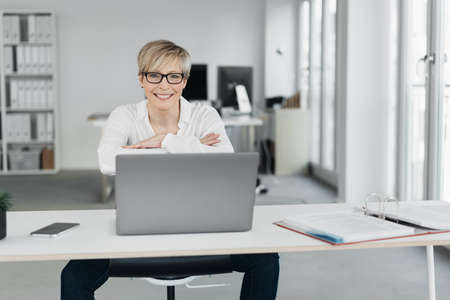 Happy relaxed businesswoman with a beaming friendly smile seated at an office table working at a laptop looking at the camera, with high key copy space