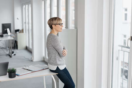 Businesswoman taking a break in the office sitting perched on the edge of a table looking out of a window