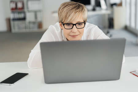 Businesswoman wearing spectacles leaning forwards on the desk concentrating on her work as she reads on her laptop computer in close up