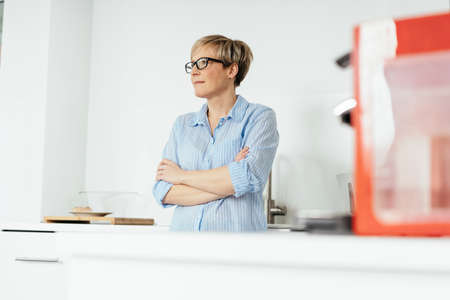 Thoughtful woman standing in her kitchen with folded arms looking off to the side with a contemplative expression with copy space