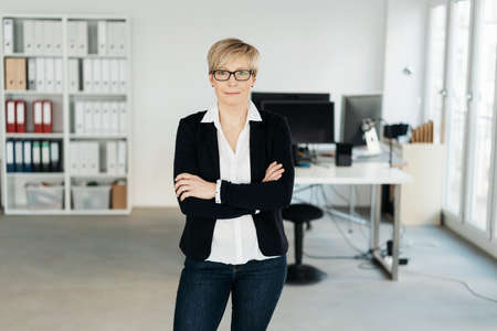 Smart female business executive standing with folded arms inside a spacious high key modern office looking thoughtfully at the camera with a quiet smile
