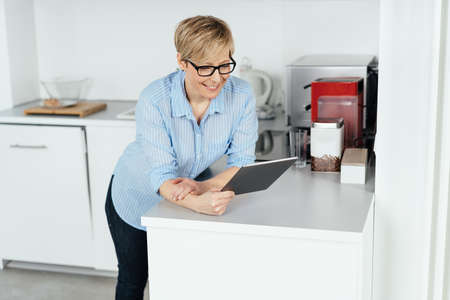 Happy woman relaxing in her kitchen with a tablet pc smiling as she reads online while leaning on a counter