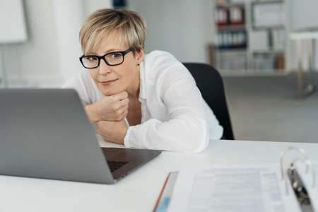 Thoughtful woman wearing glasses working in an office looking aside with a serious expression as she takes a break from her laptop balancing her chin on her hands Standard-Bild
