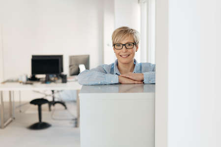 Happy friendly relaxed businesswoman wearing spectacles standing leaning on a cabinet in the office smiling at the camera