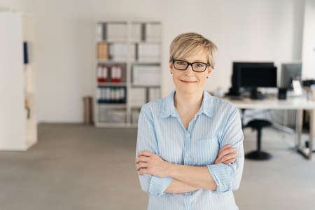 Friendly relaxed confident office worker standing with folded arms in a spacious open plan office smiling at the camera