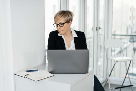 Businesswoman reading from a journal as she works at a laptop computer in a bright office with copy space seated at a small desk Standard-Bild