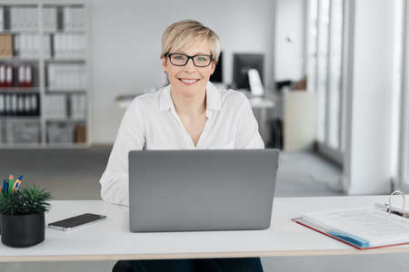 Friendly businesswoman looking at the camera with a smile as she sits behind a laptop computer at a table in a high key office Standard-Bild