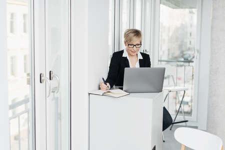 Smart businesswoman wearing glasses sitting working on a laptop computer taking notes in a journal in a bright office with copy space