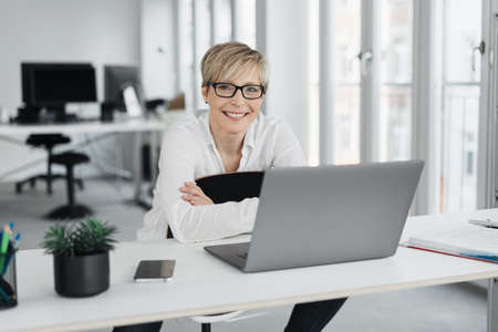 Friendly relaxed businesswoman or office worker seated at a laptop computer on a table smiling happily at the camera