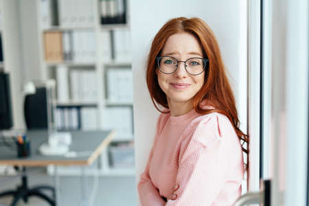 Cute charismatic young woman wearing glasses raising her eyebrows in amusement as she grins at the camera indoors in an office