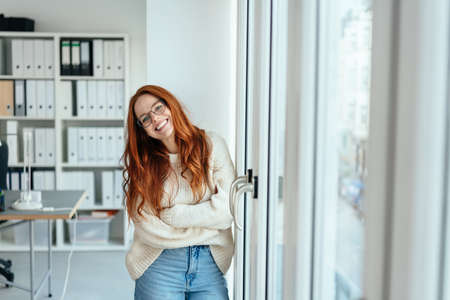 Happy relaxed smiling young businesswoman in casual jeans standing next to glass entrance doors in a high key modern office