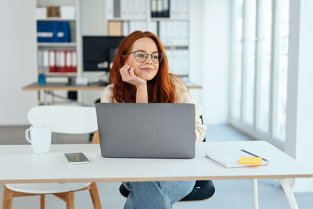 Bored young businesswoman watching to the side with her chin on her hand as she sits at her desk in a bright sunny office