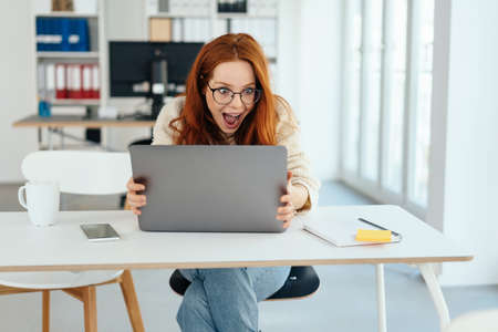 Excited young businesswoman or student in casual jeans sitting at an office table staring at her laptop with wide eyes and open mouth