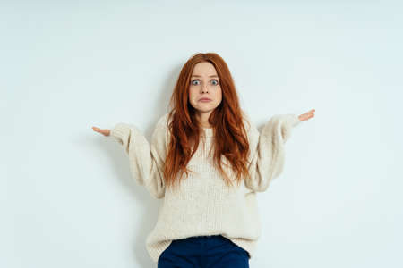 Confused young woman shrugging her shoulders to show her ignorance with a wide eyed grimace against a white interior wall with copy space Standard-Bild