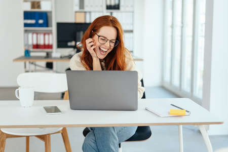 Happy young businesswoman sitting laughing with glee at her laptop computer in a bright airy modern office with copy space