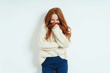 Bashful young woman hiding behind her hand and tress of her long red hair as she looks coyly at the camera against a white interior wall with copy space