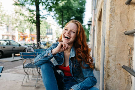 Vivacious young woman laughing uproariously at the camera as she enjoys a good joke while seated on top of a table at an empty outdoor restaurant in town Banque d'images