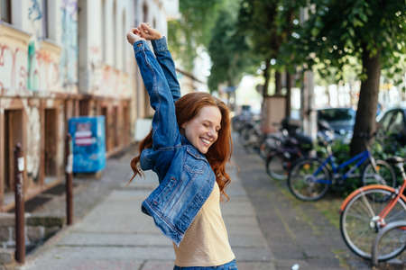 Young woman celebrating with raised arms and a happy smile on an urban street as she turns back towards the camera