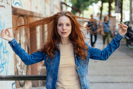 Playful young woman pulling at her long red hair holding strands up in her hands with a quirky smile outdoors in town Banque d'images