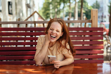 Laughing young woman holding a mobile phone as she sits at an outdoor restaurant table in a town alone