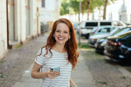 Happy grinning woman holding a mobile phone on a quiet urban street as she looks attentively at the camera