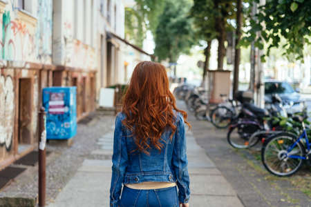 Young woman with long curly red hair wearing denims walking away down an urban street Banque d'images