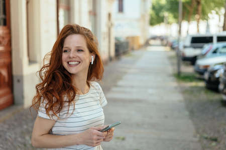 Happy young woman turning aside with a warm friendly smile as she stands waiting on a sidewalk in town