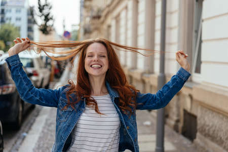 Happy young woman playing with her long red hair smiling happily at the camera as she pulls strands up in her hands on an urban street