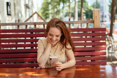 Happy young woman relaxing at a restaurant table grinning a she reads a message or streams media on a mobile phone Banque d'images
