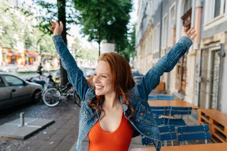 Happy casual young redhead woman rejoicing in town stretching up her arms and looking aside with a beaming smile of pleasure