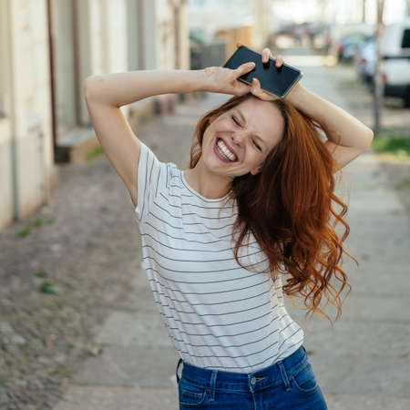 Happy young woman with beaming smile and eyes tight shut holding her mobile above her head as she grins at the camera on a quiet urban street