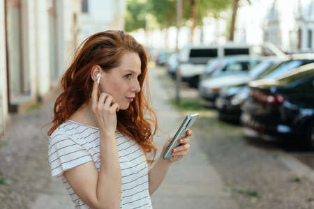 Young woman listening on an earbud as she holds her smartphone in her hand on an urban street