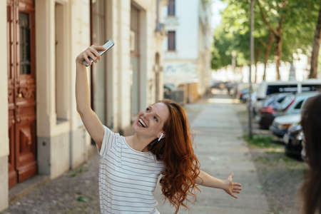 Vivacious young woman posing for a selfie on her smartphone on a quiet urban street grinning for the camera Banque d'images
