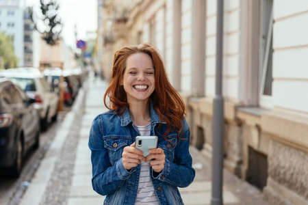 Young woman with a happy toothy grin holding a mobile in her hands on an urban street facing the camera Banque d'images