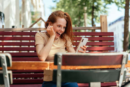 Young woman looking at her mobile in amazement and delighted surprise as she sits outdoors at an urban restaurant Banque d'images