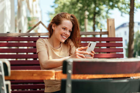 Smiling young woman reading a phone message or streaming media at an outdoor restaurant table on her smartphone