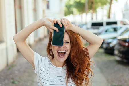 Laughing young woman holding up her mobile with the screen to the viewer on a quiet urban street