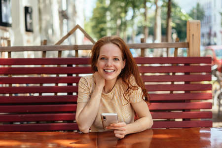 Young woman sitting at an outdoor restaurant table holding a mobile phone looking attentively at the camera