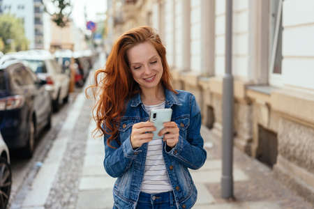Young redhead woman reading on her mobile phone with a quiet smile of satisfaction in an urban street
