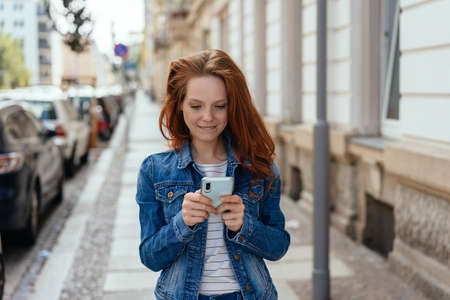 Young redhead woman in denim checking a message on her phone standing on a quiet urban street reading with an engrossed expression