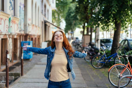 Happy young woman rejoicing with outstretched arms and a beaming smile on a sidewalk on a quiet urban street