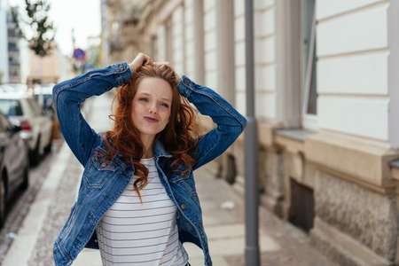 Cute charismatic young woman with playful grin standing with her hands raised on an urban street in a denim jacket