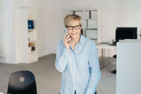 Cheerful mature blonde woman wearing blue shirt talking on mobile phone at office Banque d'images