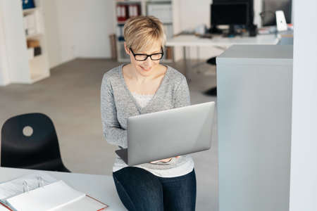 Smiling short-haired blonde woman working on laptop while sitting on desk at office Standard-Bild