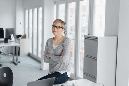 Middle-aged blond woman with short haircut, in glasses and gray pullover, sitting on the edge of the office desk with folded arms and looking aside with calm and serious face. Portrait with copy space