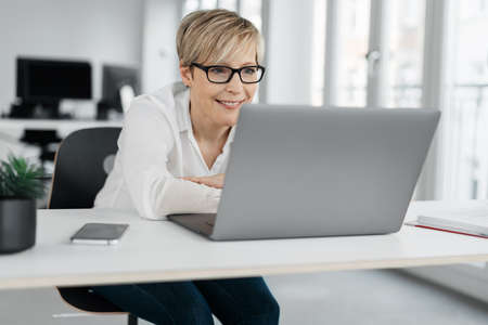 Smiling businesswoman wearing spectacles sitting resting her folded arms on the table reading on her laptop in a high key office