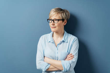 Thoughtful woman wearing glasses standing with folded arms looking aside with a pensive expression over a blue studio background with copy space