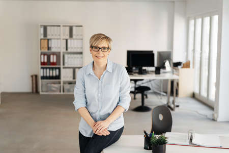 Smiling middle-aged woman with blond short hair, wearing glasses and blue shirt, sitting on the edge of a in an empty office interior and looking at camera. Half-length front portrait with copy space