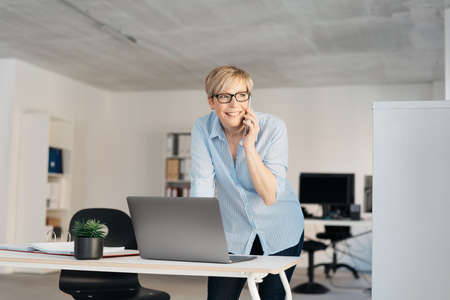 Smiling businesswoman with short haircut, in glasses and blue shirt, standing at the office desk in front of laptop, talking by mobile phone and looking aside. Low angle portrait with copy space Banque d'images