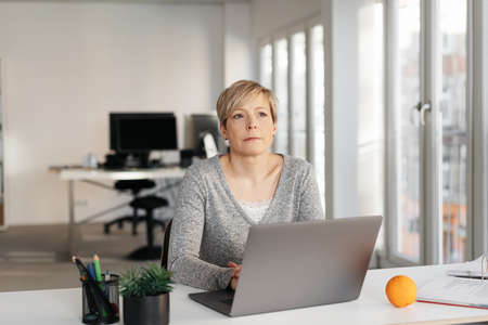 Thoughtful businesswoman sitting at her laptop computer staring up into the air with a serious expression in a high key office with copy space